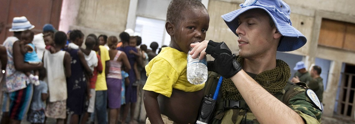 Argentinean UN peacekeeper holds a baby download during distribution of water and food to victims of tropical storm Hanna